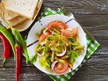 沙拉青豆,蕃茄,在一个木食家莴苣的营养,在红辣椒开胃午餐上添面包 库存图片