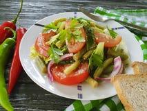 沙拉青豆,蕃茄,在一个木食家莴苣,面包红辣椒开胃午餐 免版税库存图片