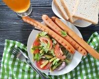 沙拉青豆,蕃茄,油煎了在一串木背景烤肉的晚餐香肠快餐传统开胃菜啤酒 库存照片