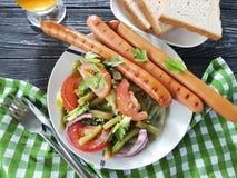 沙拉青豆,蕃茄,油煎了在一串木背景烤肉的香肠快餐传统开胃菜啤酒 库存照片