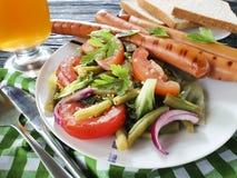 沙拉青豆,蕃茄,油煎了在木背景的香肠传统开胃菜啤酒 库存照片