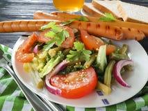 沙拉青豆,蕃茄,油煎了香肠在木背景的开胃菜啤酒 免版税库存照片