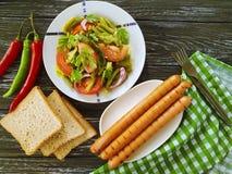 沙拉青豆,蕃茄,食家晚餐营养油煎了在木背景的香肠,开胃的红辣椒 免版税图库摄影