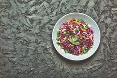 沙拉,健康食物 红叶卷心菜沙拉 新鲜蔬菜沙拉用紫色圆白菜,白椰菜,沙拉,在一把黑暗的黏土弓的红萝卜 免版税库存图片