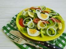 沙拉,黄瓜,鸡蛋,蕃茄,维生素准备了在白色木背景的自创开胃菜开胃菜葱 免版税库存图片