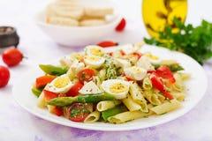 沙拉- penne面团用芦笋,蕃茄,鹌鹑蛋,无盐干酪 免版税库存照片