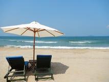 沙滩伞和两晒黑床以横向格式 库存照片