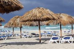 沙滩伞和绿宝石水背景 免版税库存图片