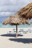 沙滩伞和绿宝石水背景 免版税图库摄影