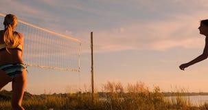 沙滩排球比赛女孩击中了在慢动作的球在沙子的日落 影视素材