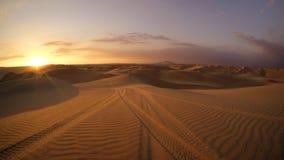 沙漠在与沙地汽车轮胎轨道的日落小时在前景的沙子 免版税库存图片