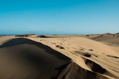 沙漠沙丘底层视图在日落的与艰苦击中从给的太阳感觉上温暖和热与没人maspalomas的 库存图片
