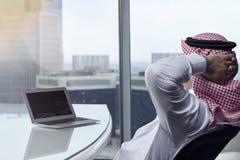 沙特阿拉伯在工作冥想的人观看的膝上型计算机 免版税库存图片
