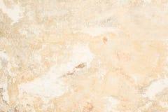 黄沙颜色老古色古香的墙壁的纹理,那里是膏药白色防护层数的破裂从作用的 免版税库存图片