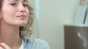 沙龙的一可爱的年轻女人检查她的在镜子的头发 影视素材