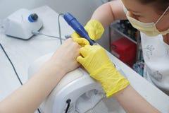 沙龙钉子服务的女孩 钉子的对准线使用一个电机器的 免版税库存图片