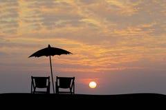 沙滩伞和太阳床在日落期间 一个简单的生活方式剪影 放松 免版税库存图片