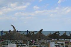 沙滩伞-和在海滩的冷的风暴日在罗马尼亚海边在Neptun,康斯坦察罗马尼亚 免版税库存照片