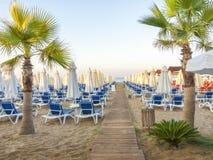 沙滩向有木小径的,太阳床,伞, pa海 免版税库存照片