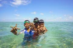沙巴,马来西亚- 11月19 :未认出的Bajau Laut孩子在2015年11月19日的马伊加海岛拿着一个美丽的海星 免版税库存图片