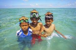 沙巴,马来西亚- 11月19 :未认出的Bajau Laut孩子在2015年11月19日的马伊加海岛拿着一个美丽的海星 免版税库存照片