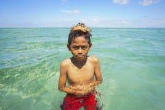 沙巴,马来西亚- 11月19 :未认出的Bajau Laut孩子在2015年11月19日的马伊加海岛拿着一个美丽的海星 图库摄影