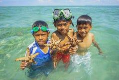 沙巴,马来西亚- 11月19 :未认出的Bajau Laut孩子在2015年11月19日的马伊加海岛拿着一个美丽的海星 库存图片