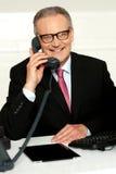 沟通与他的客户机的微笑的变老的人 库存图片