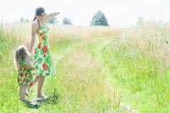 沟通与农村农场马路的小女儿的俏丽的妇女 图库摄影
