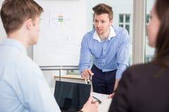 沟通与同事的商人在会议在办公室 免版税库存图片