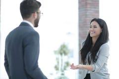 沟通与同事的女商人在办公室 免版税库存照片