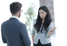 沟通与同事的女商人在办公室 免版税库存图片