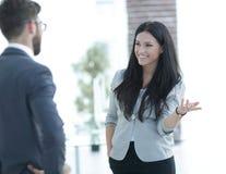 沟通与同事的女商人在办公室 图库摄影
