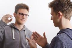 沟通与手势语的两个少年 免版税图库摄影