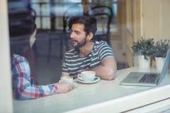 沟通在咖啡馆的夫妇 图库摄影
