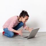 沟通在地板上的膝上型计算机的激动的美丽的少妇 免版税库存图片