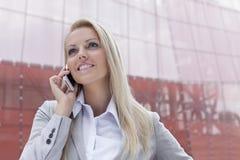 沟通在巧妙的电话的愉快的年轻女实业家反对办公楼 库存照片
