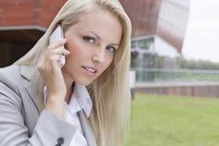 沟通在手机的美丽的年轻女实业家特写镜头画象反对办公楼 库存照片