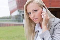 沟通在手机的美丽的年轻女实业家特写镜头画象反对办公楼 图库摄影