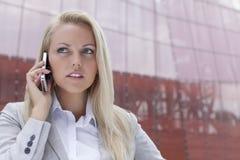 沟通在手机的年轻女实业家特写镜头反对办公楼 库存照片