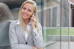 沟通在手机的年轻女实业家画象,当倾斜在玻璃墙时 免版税库存图片