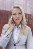 沟通在手机的年轻白肤金发的女实业家反对办公楼 库存图片