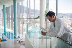 沟通在电话的愉快的人在豪华温泉旅馆里 免版税库存照片