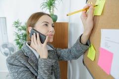 沟通在证券交易经纪人行情室的女性办公室工作者 免版税图库摄影