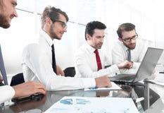沟通的商人工作和,当坐在办公桌时 库存图片