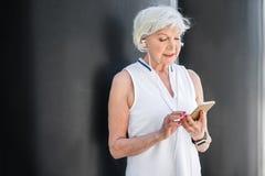 沟通通过手机的爽快年长妇女外面 库存图片