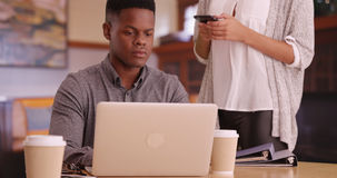 沟通年轻非裔美国人的millennials,当工作在计算机和短信上时 免版税库存图片
