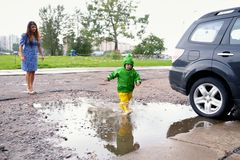 没得到的湿衣裳愉快的小男孩充当在街道上的水池有母亲的 图库摄影