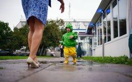 没得到的湿衣裳愉快的小男孩充当在街道上的水池有母亲的 免版税库存图片