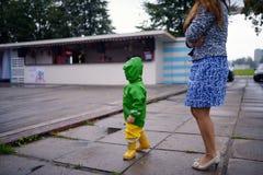 没得到的湿衣裳愉快的小男孩在有母亲的街道上使用 免版税库存照片